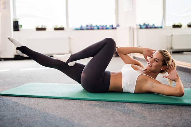 young female athlete exercising sit-ups in a health club. - sit ups stock photos and pictures