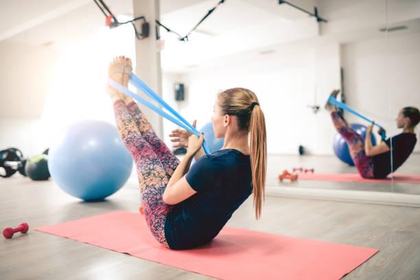 junge sportlerin mit gummiband im fitness-studio trainieren - leinenhosen frauen stock-fotos und bilder