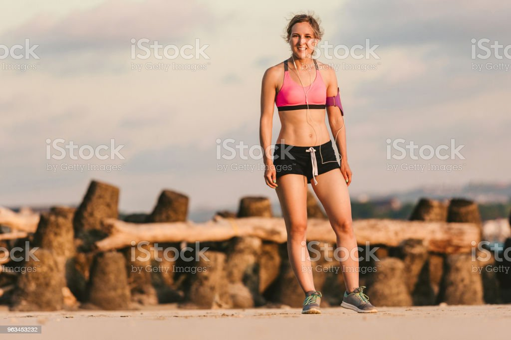 young female athlete in earphones with smartphone in running armband case standing on sandy beach - Zbiór zdjęć royalty-free (Aktywny tryb życia)