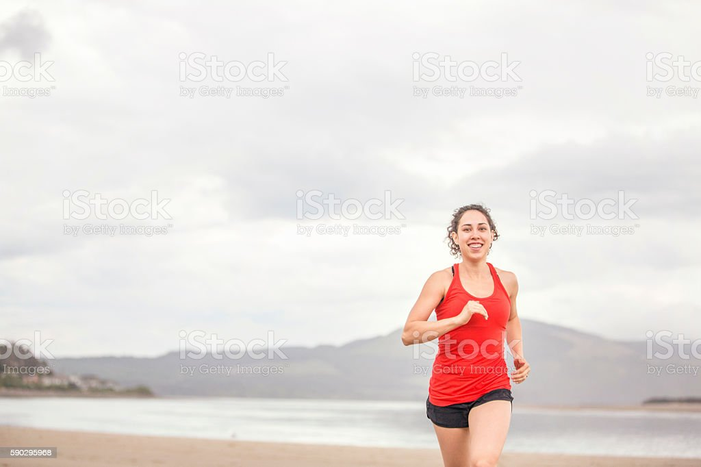 Young female athlete jogging at the beach royaltyfri bildbanksbilder