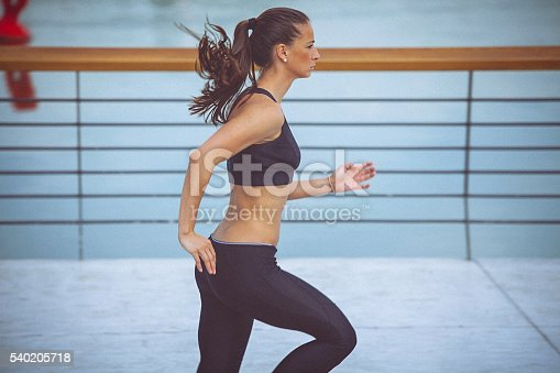 494003079istockphoto Young female athlete jogging on the waterfront 540205718