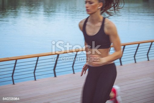 494003079istockphoto Young female athlete jogging on the waterfront 540205984