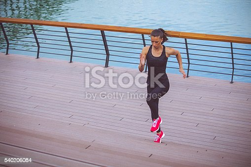 494003079istockphoto Young female athlete jogging on the waterfront 540206084
