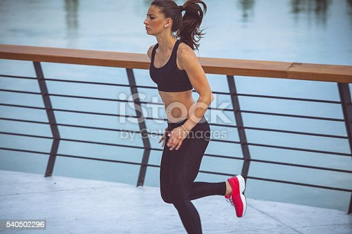 494003079istockphoto Young female athlete jogging on the waterfront 540502296