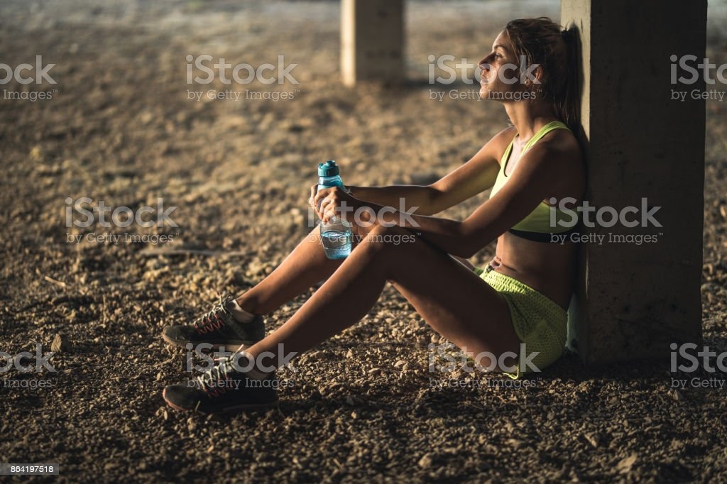 Young female athlete leaning on a pillar while taking a water break from sports training. royalty-free stock photo