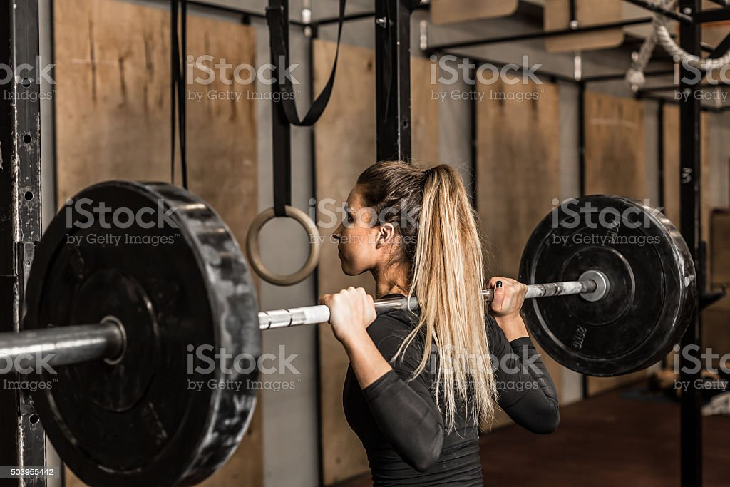 Young female athlete performed squats in the gym stock photo
