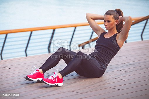 istock Young female athlete performs ab crunches outdoors 540206540