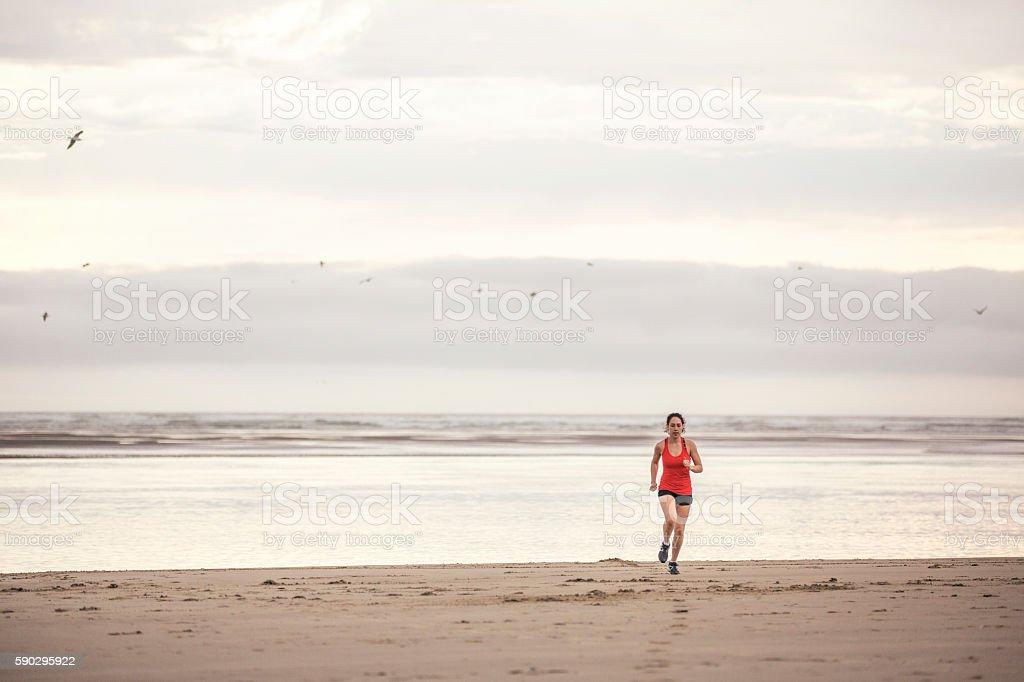 Young female athlete running across the sand at the beach royaltyfri bildbanksbilder
