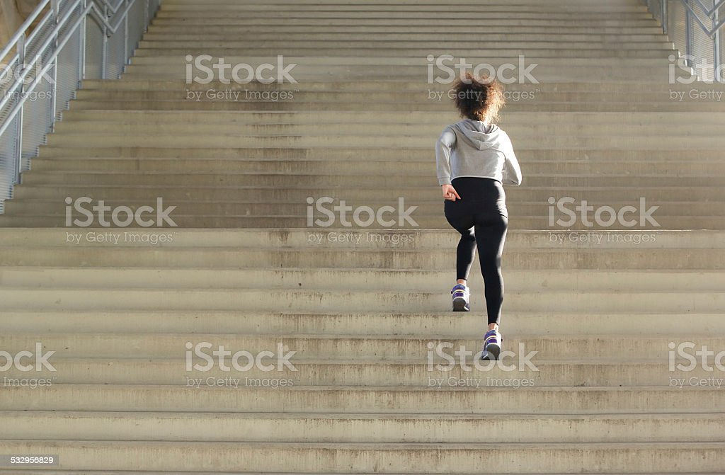 Young female athlete running up stairs stock photo