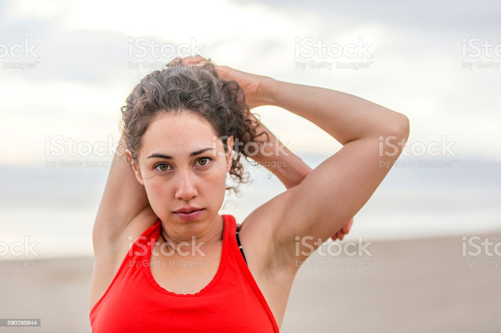 Young female athlete stretching before her run at the beach royaltyfri bildbanksbilder
