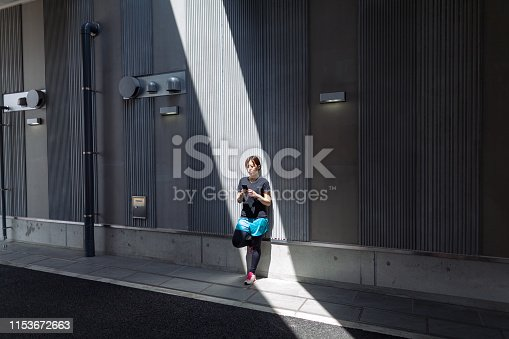 A young female athlete is using a smart phone in the city.