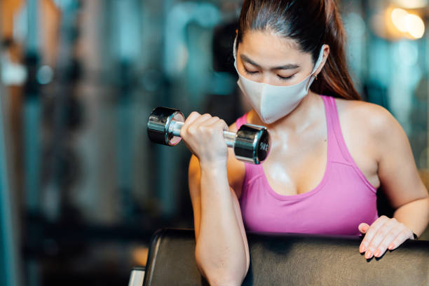 Young female athlete wearing protective face mask and doing strength training with dumbbell in gym stock photo