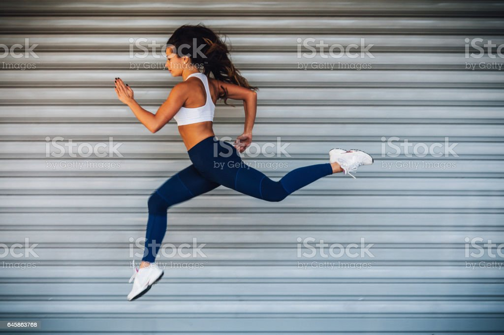 Young female athlete woman running jumping stock photo