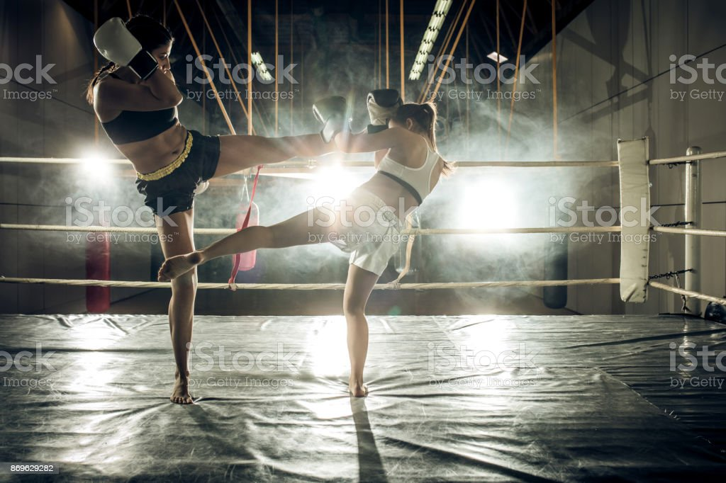 Full length of two female kick boxers having a fight in a boxing ring.