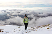 Young female backpacker walks on the mountain
