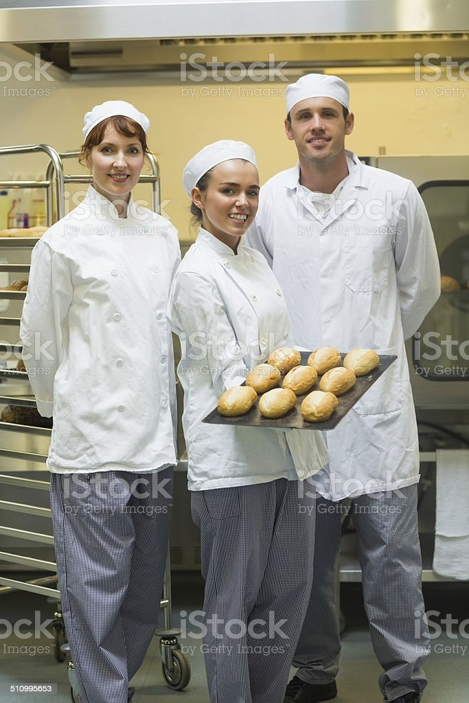 Young female baker presenting some rolls stock photo