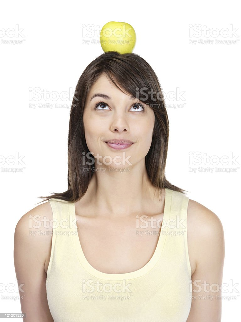 Young female balancing an apple on head against white royalty-free stock photo