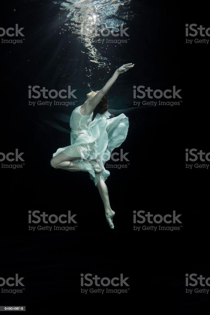 Young female ballet dancer dancing underwater stock photo