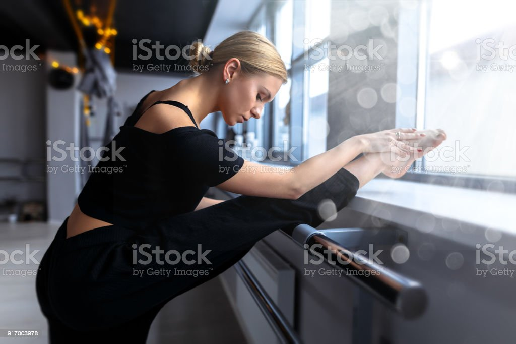 Young female ballet dancer is stretching in the studio with white walls stock photo