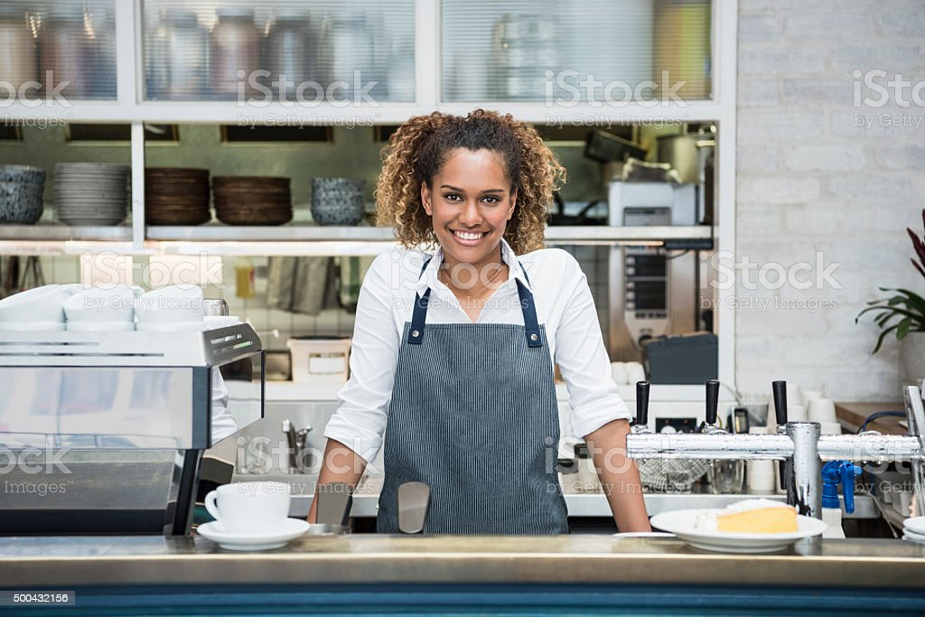 Young female barista at counter in cafe, portrait stock photo