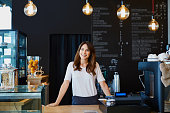 istock Young female barista standing behind the bar in cafe smiling 964217064