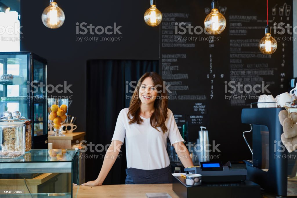 Young female barista standing behind the bar in cafe smiling stock photo