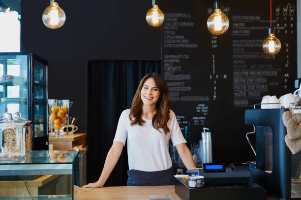 young female barista standing behind the bar in cafe smiling - owner stock pictures, royalty-free photos & images