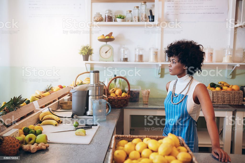 Young female bartender standing at juice bar counter stock photo