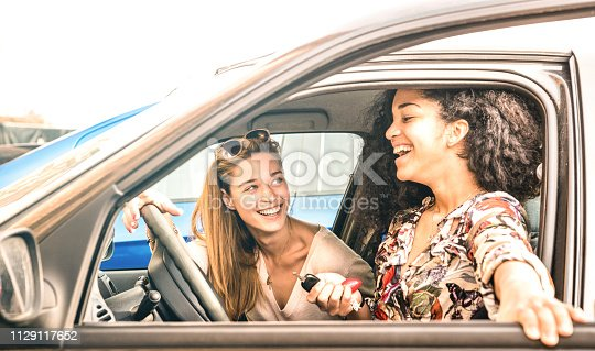 Young female best friends having fun at car roadtrip moment - Transportation concept and urban ordinary life with women girlfriends at happy travel vacation on the road - Bright azure filter