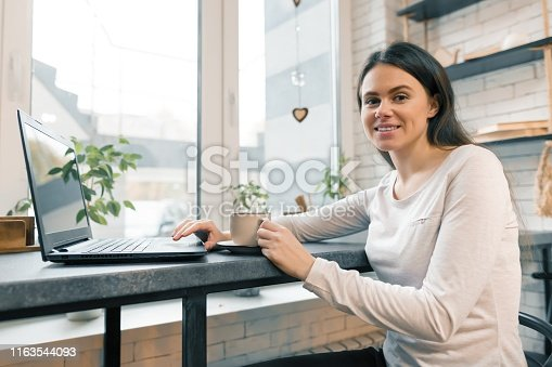 Young female blogger in coffee shop with laptop computer and cup of fresh coffee