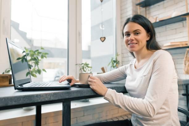 Joven bloguera en cafetería con computadora portátil - foto de stock