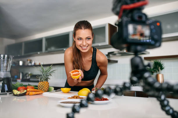 Young female blogger recording content for videoblog in Kitchen. stock photo