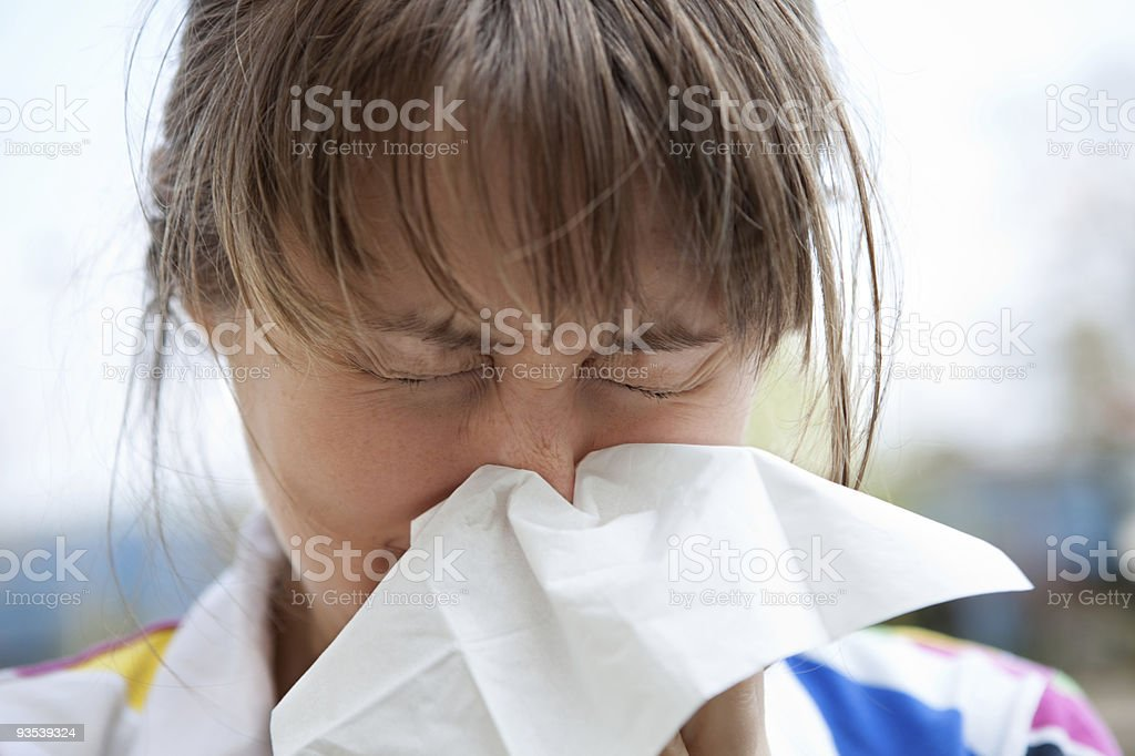 A young female blowing her nose with a tissue royalty-free stock photo