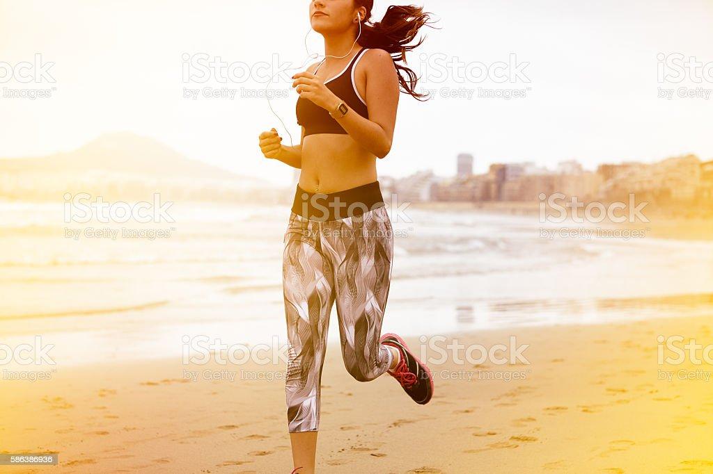 Young female body running along beach stock photo