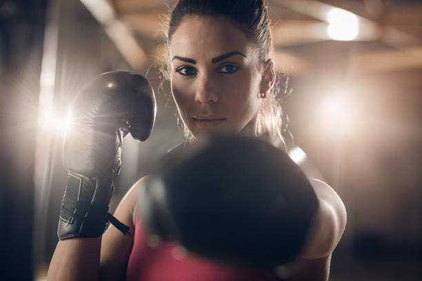 Young female boxer on a sports training in a gym. stock photo