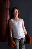 10-year-old girl in boxing gear trying her hardest to look mean and tough.
