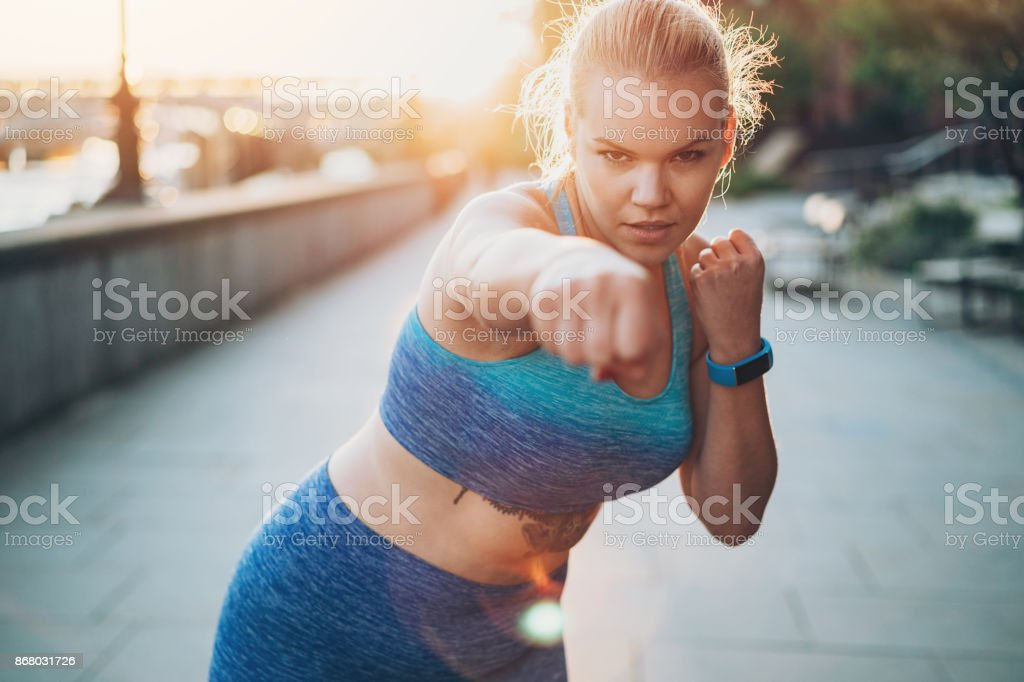Young female boxer training outdoors stock photo