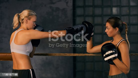 Young female boxer working on right hand punch with her trainer on squared ring