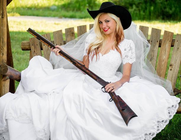 junge frau braut hält eine schrotflinte - shotgun wedding stock-fotos und bilder