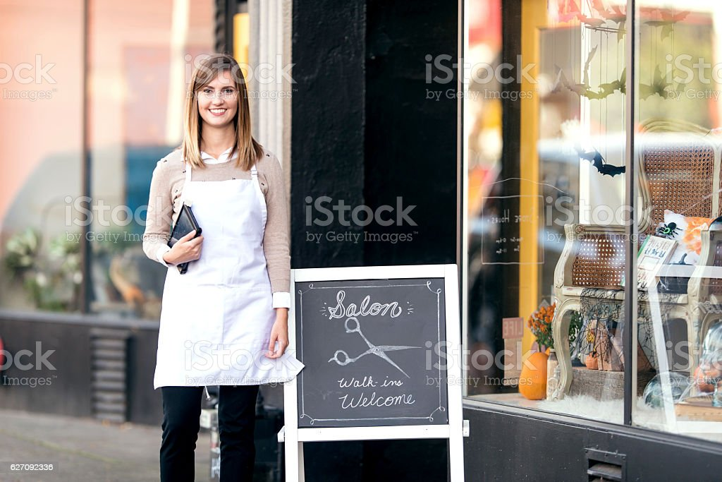 Young female business owner standing outside her salon shop stock photo