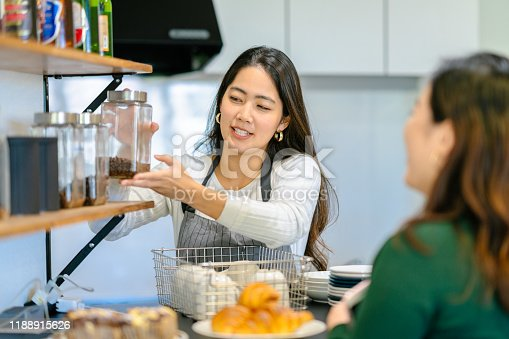 597640822 istock photo Young female cafe owner explaining coffee beans 1188915626