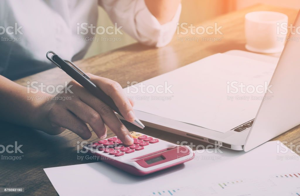 Young female calculates cost on desk at home office stock photo
