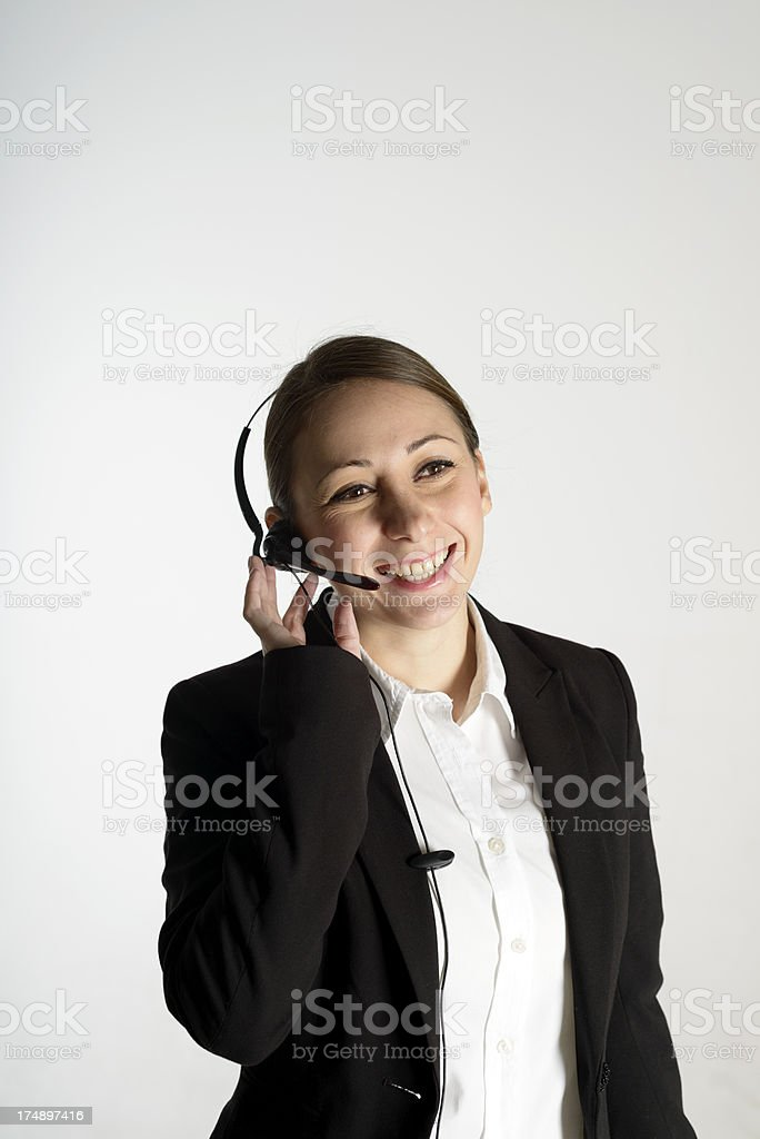 Young female call centre employee wearing a headset, white background royalty-free stock photo