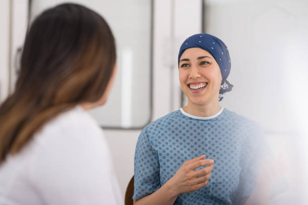 young female cancer patient meets with her doctor - cancer patient stock pictures, royalty-free photos & images