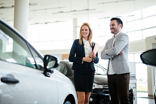 istock Young female car sales consultant working in showroom 1167979303