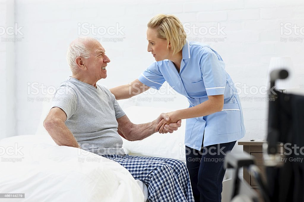 Young female caregiver helping senior man stock photo