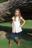 istock Young female caucasian child posing in front of a large tree at a public park 1253837726