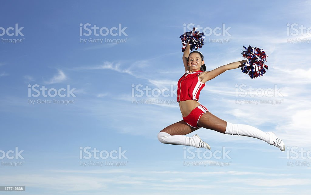 Young female cheerleader jumping in the air with pom-poms stock photo