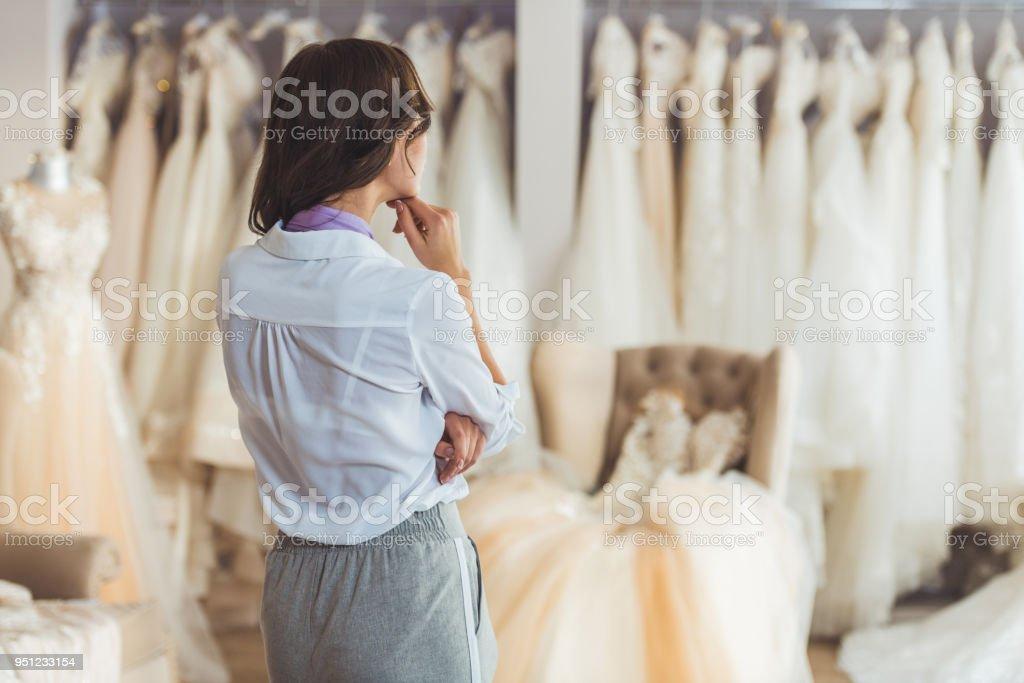 Young female choosing dress in wedding salon stock photo