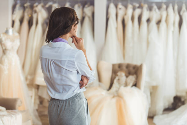 Young female choosing dress in wedding salon stock photo